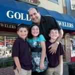 Family in front of Gold Rush Jewelers store that offers jewelry and watch repair.