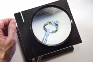 A diamond ring being appraised by the jeweler with a magnifying glass. Jewelry Appraisals