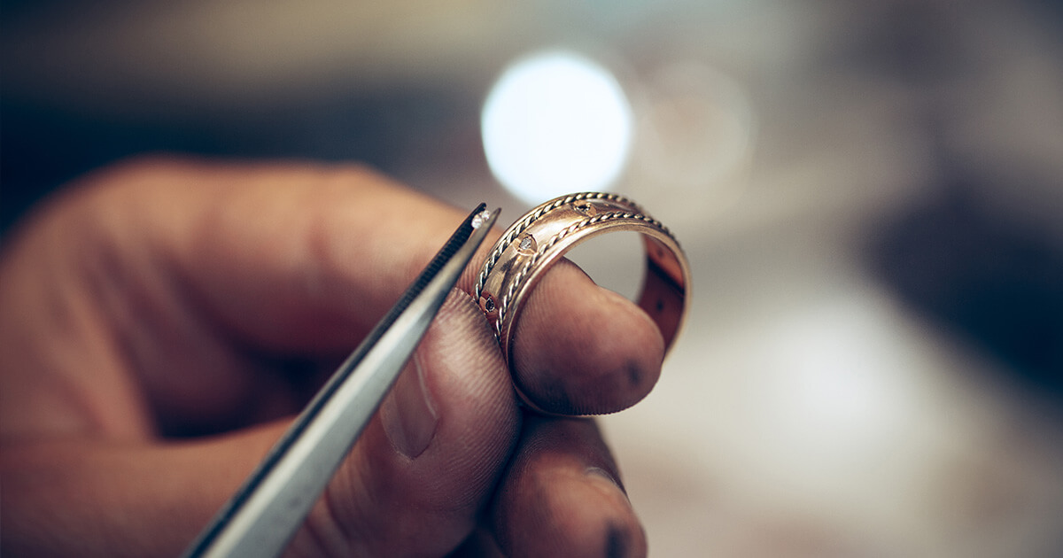Jeweler repairing a golden ring. Jewelry services